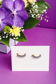 거짓 속눈썹과 보라색 꽃 조성. 미용 제품, 눈용 화장품