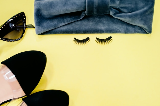 False eyelashes on color background, flat lay