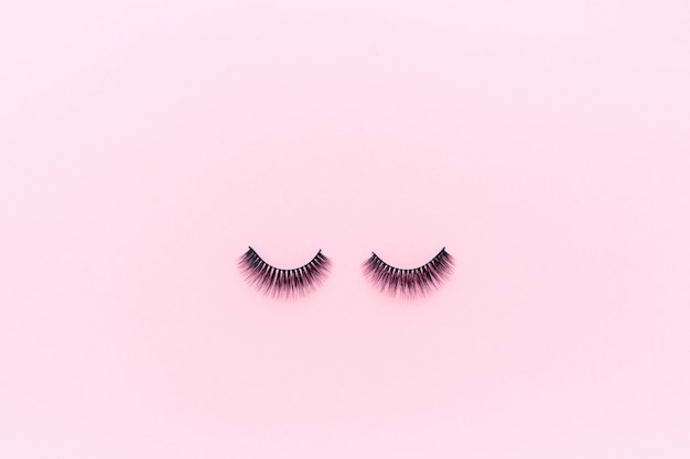 False eyelashes lying on pink.