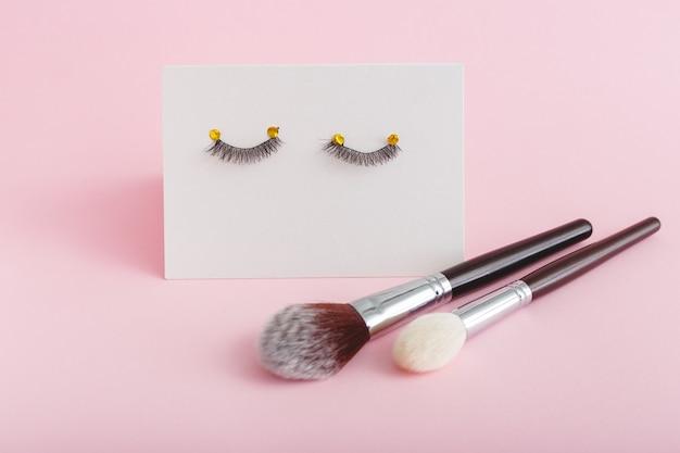 분홍색 배경에 가짜 속눈썹 메이크업 브러쉬. 미용 제품, 눈용 화장품, 속눈썹 연장, 미용실 또는 뷰티 스파 살롱 개념.