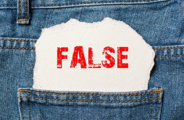 False on white paper in the pocket of blue denim jeans