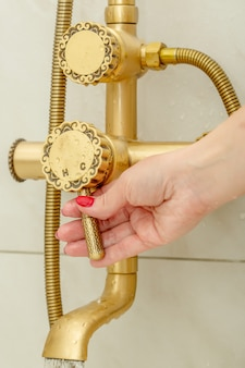 Famale hand switches a shower faucet in vintage style cold and hot water