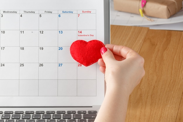Famale hold red heart on calendar