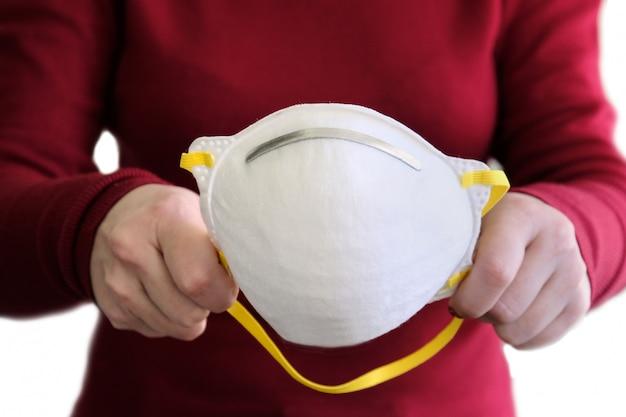 Famale вручает держать белую защитную маску изолированный на белизне.