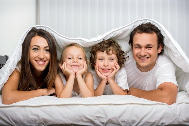 毛布の下のベッドで子供連れの家族。