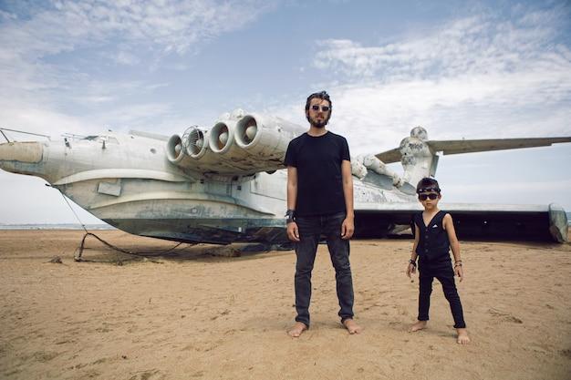 ダゲスタンの海沿いの放棄されたエクラノプラン飛行機に立っている家族の少年とロッカーの服を着た父親