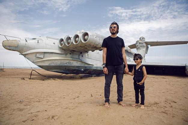 家族の少年とロッカーの服を着た彼の父親は、放棄されたエクラノプラン飛行機に立っています
