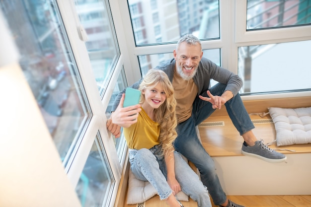 가족. 백발의 성숙한 남자와 그의 딸이 함께 기분이 좋다