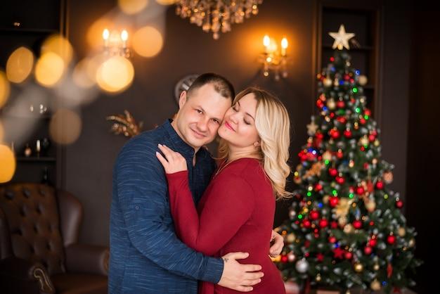 가족, 한 남자와 한 여자가 크리스마스 트리를 배경으로 포옹합니다. 새해 복 많이 받으세요