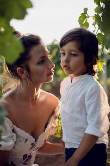 イタリアの夏にブドウ園を歩いている息子と一緒にドレスを着た母親の家族