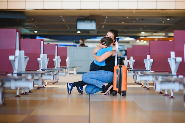 Family at airport before flight. mother and son waiting to board at departure gate of modern international terminal. traveling and flying with children. mom with baby and toddler boarding airplane.