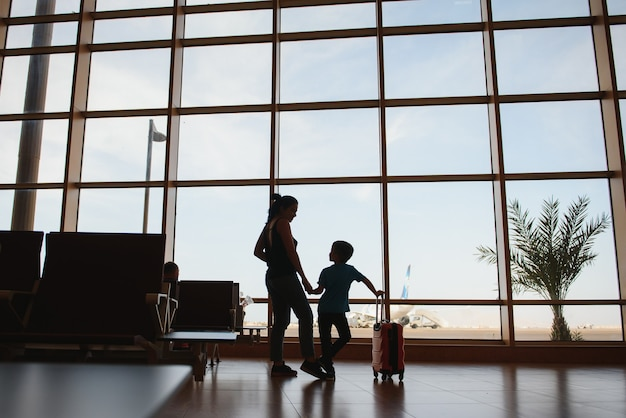 Family at airport before flight. mother and son waiting to board at departure gate of modern international terminal. traveling and flying with children. mom with kid boarding airplane. yellow family