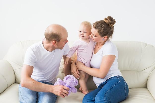 家族と子供たちのコンセプトは、家で生まれたばかりの赤ちゃんの娘を抱いて笑顔の母と父