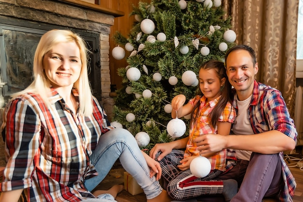Семья и новогодняя елка в старом деревянном доме