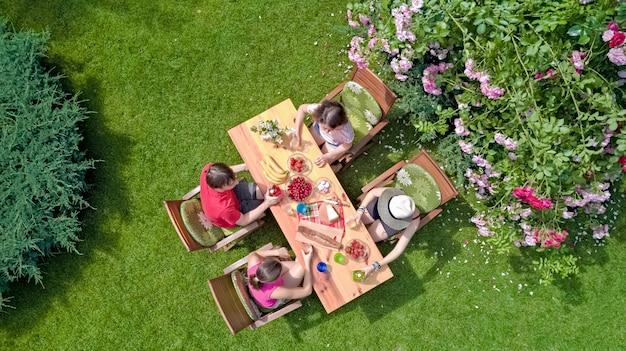 家族や夏のガーデンパーティーで屋外で一緒に食べる友達。上から食べ物や飲み物を持つテーブルの空撮。レジャー、休日、ピクニックのコンセプト