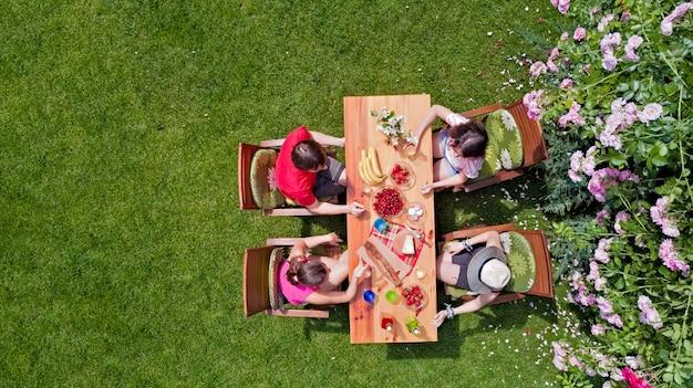家族や夏のガーデンパーティーで屋外で一緒に食べる友達。上から食べ物や飲み物をテーブルの空撮。レジャー、休日、ピクニックのコンセプト