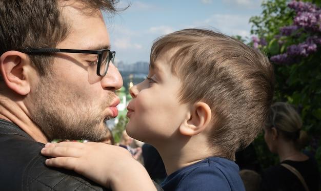 家族と幸せなライフスタイルのコンセプト。父と3歳の息子は愛情を込めてお互いを見つめています。父は彼の幼い息子にキスします
