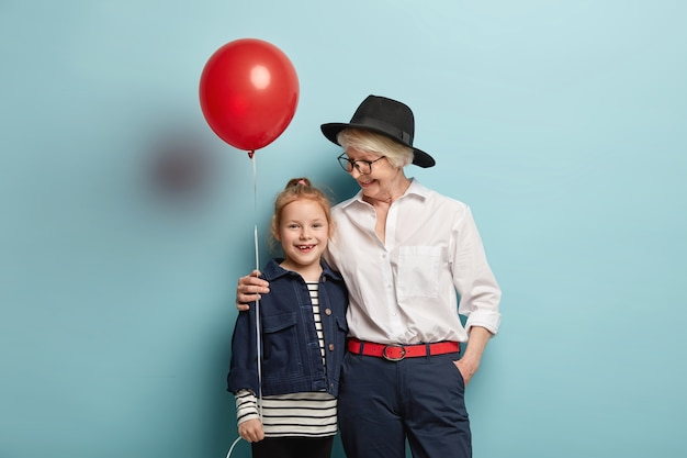 가족과 휴가 개념. 세련된 옷을 입은 돌보는 회색 머리 할머니, 작은 손녀를 안고, 함께 어린이 날을 축하하고, 장식 풍선이있는 파란색 벽 위에 서 있습니다.