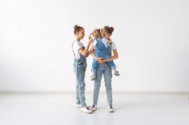 家族と愛の概念-コピースペースで白い背景を抱き締める3人の姉妹