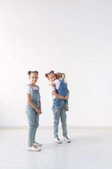 家族と愛の概念-白い背景の上に抱き締める3人の姉妹。