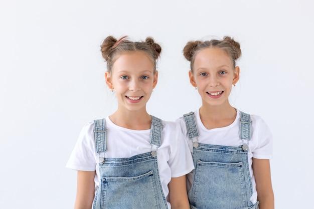 Концепция семьи и любви - две улыбающиеся сестры-близнецы обнимаются над белой стеной.