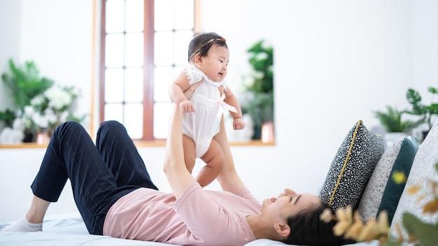 가족 및 모성 개념 집에서 작은 아기 아들과 함께 행복한 젊은 아시아 어머니