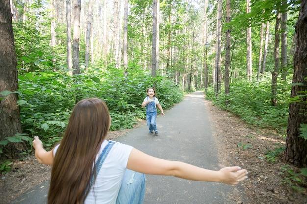 가족과 자연 개념-매력적인 젊은 여자가 공원에서 그녀의 작은 딸과 함께 재미가 있습니다.