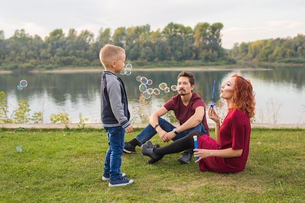 가족과 자연 개념-어머니, 아버지와 화려한 비누 거품을 가지고 노는 자녀