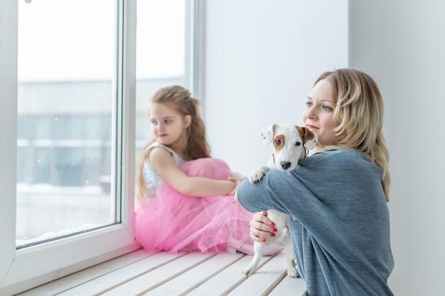 Концепция семьи и домашних животных - мать и дочь, играя с собакой джек-рассел-терьер дома.