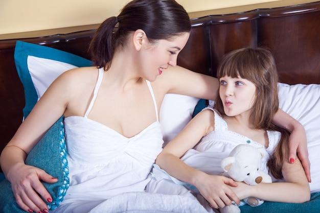 家族と関係の概念。子供を見て歯を見せる母親、娘はお母さんに空気キスをします。スタジオショット