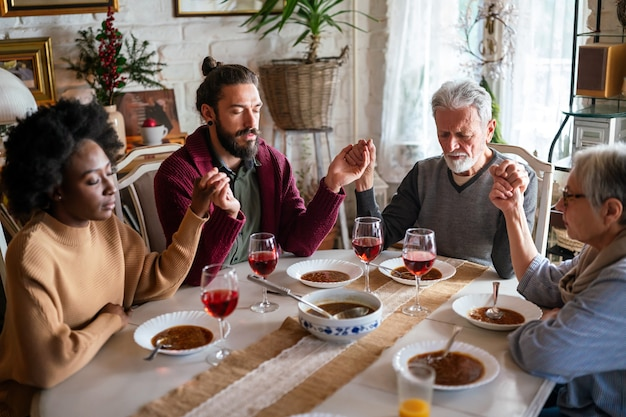 가족 및 종교 개념입니다. 식탁에 앉아서 식사 전에 기도하는 음식을 가진 다민족 사람들의 그룹