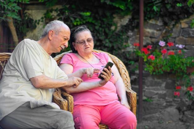 家族と技術の概念。庭で屋外でスマートフォンを使用して老夫婦