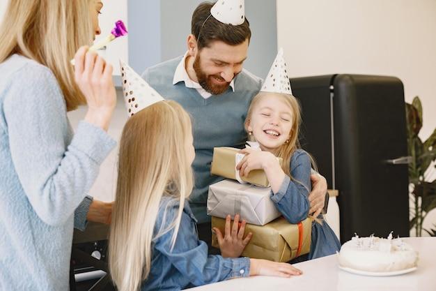 가족과 두 딸이 부엌에서 생일을 축하합니다. 사람들은 파티 모자를 쓴다. 소녀는 선물 상자를 유지합니다.