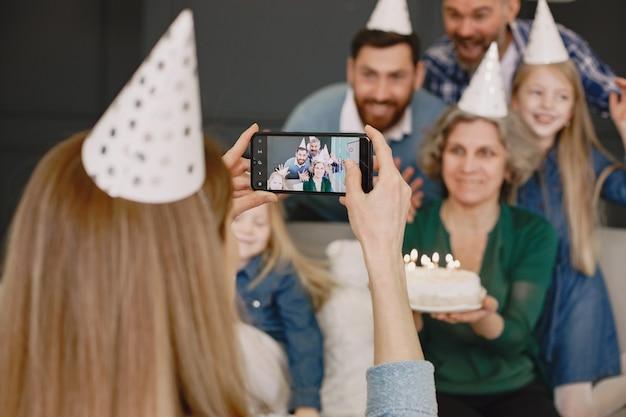 Семья и две их дочери празднуют день рождения двое мужчин и две маленькие девочки сидят на диване мать фотографирует их