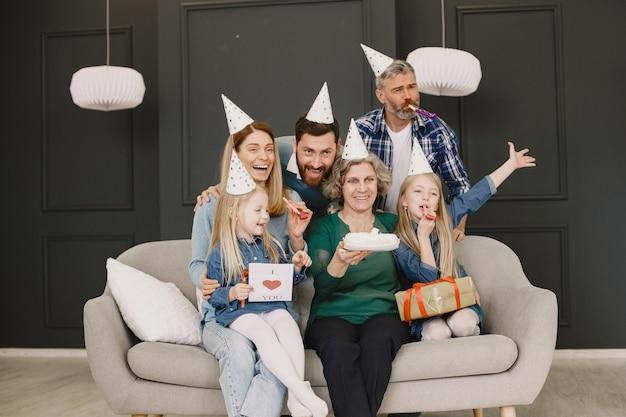 가족과 두 딸이 birthdaytwo 남자 두 여자와 두 어린 소녀가 소파에 앉아 사진을 위해 포즈를 취하고있다