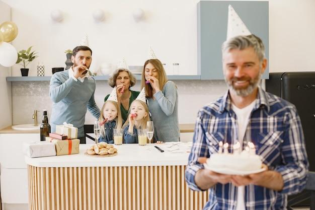 가족과 두 딸은 할머니의 생일을 축하합니다. 성인 아들은 촛불로 케이크를 유지합니다.