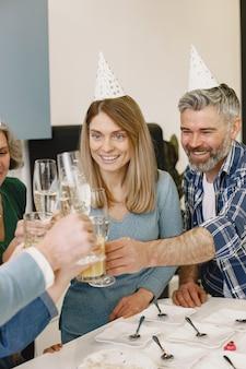 가족과 두 딸이 할머니의 생일을 축하합니다. 사람들이 샴페인으로 유리 잔을 부딪 치고 있습니다.