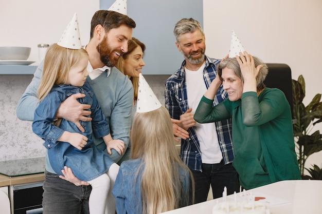 가족과 두 딸이 할머니의 생일을 축하합니다. 사람들은 파티 모자를 쓰고 있습니다.