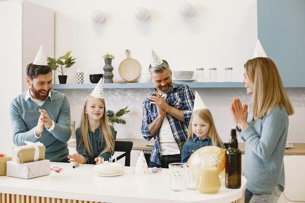 가족과 두 딸이 축하합니다. 사람들은 박수를 치며 웃습니다. 선물이 테이블 위에 있습니다.