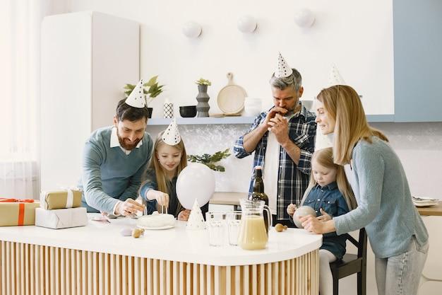 가족과 두 딸이 축하합니다. 풍선을 부는 사람들. 선물이 테이블 위에 있습니다.