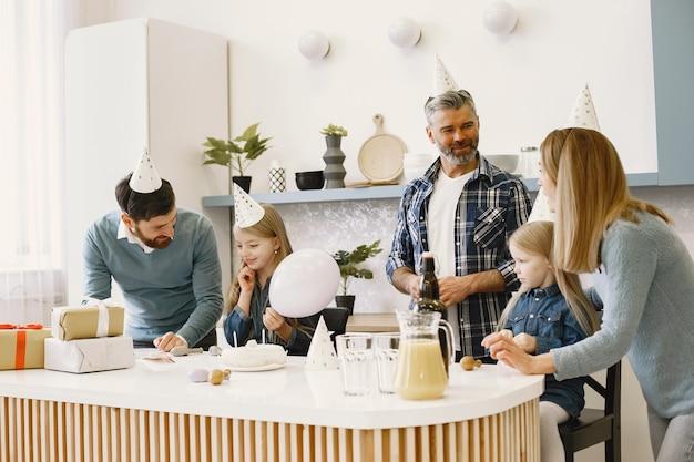 가족과 두 딸이 축하합니다. 사람들에게는 풍선이 있습니다. 선물이 테이블 위에 있습니다.