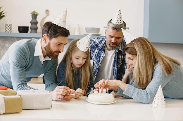 가족과 두 딸이 축하합니다. 사람들은 촛불 케이크를 찾고 있습니다.