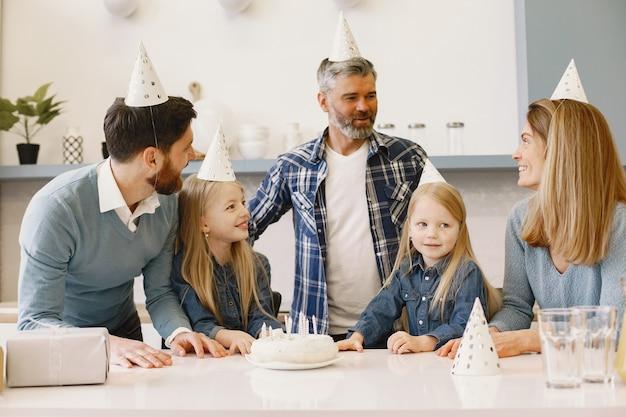 가족과 두 딸이 축하합니다. 테이블에 촛불이 달린 케이크가 있습니다.