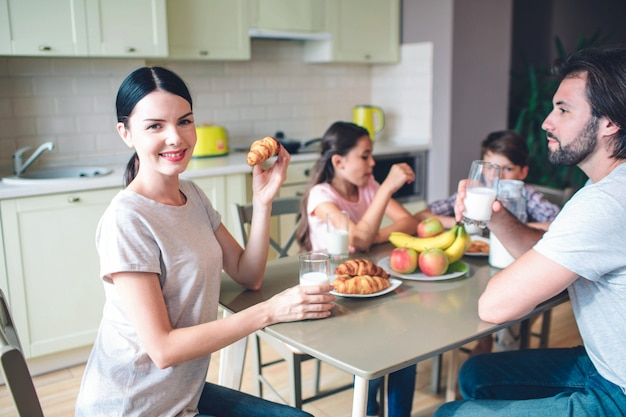 가족은 함께 테이블에 앉아 있습니다. 여자가 보인다. 그녀는 롤을 보유하고 있습니다. 다른 가족 구성원이 먹고 이야기하고 있습니다.