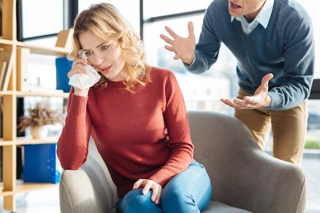家族の議論。不幸な憂鬱な女性が夫の言うことを聞き、感情を維持できずに泣いている
