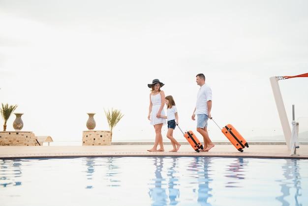 スイミングプールのそばにスーツケースを持って高級ホテルに到着する家族
