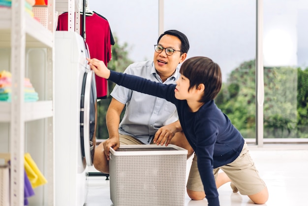 Family asian father and kid little boy son having fun doing household chores doing laundry dirty clothes into the washing machine together in laundry room at home