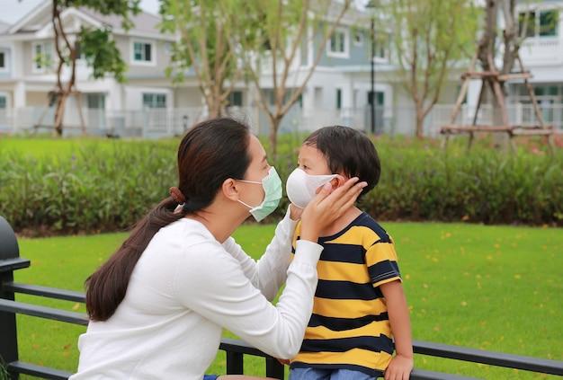 코로나바이러스와 독감 발병 동안 공공 정원에서 아들을 위해 보호용 안면 마스크를 쓴 가족 아시아 엄마