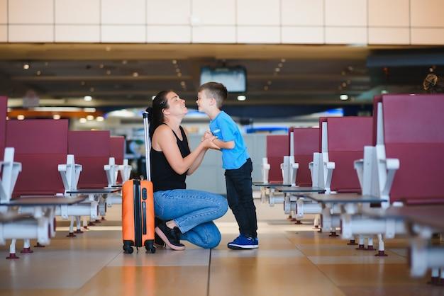 Семья в аэропорту перед полетом. мать и сын ждут посадки у выхода на посадку современного международного терминала. путешествовать и летать с детьми. мама с ребенком и малышом посадка в самолет.
