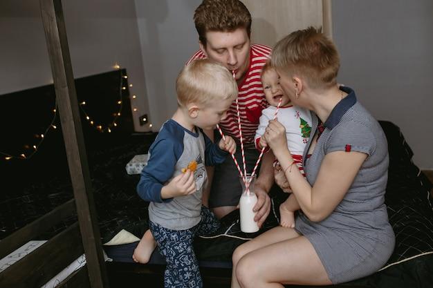 Семья дома перед рождеством пьет молоко из одной бутылки с длинной трубочкой